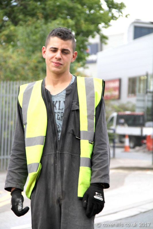 Young lad repairing the road wearing a dirty navy coverall, yellow hi-vis waistcoat. Young Lad Road Worker 6