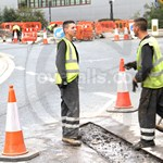 Young lad repairing the road wearing a dirty navy coverall, yellow hi-vis waistcoat