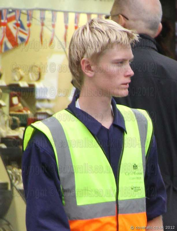 Young blonde Polish lad working as a Road Sweeper wearing a blue boilersuit/coverall and yellow hi-vis waistcoat. Young Blonde Polish Road Sweeper 1