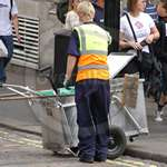 Young blonde Polish lad working as a Road Sweeper wearing a blue boilersuit/coverall and yellow hi-vis waistcoat