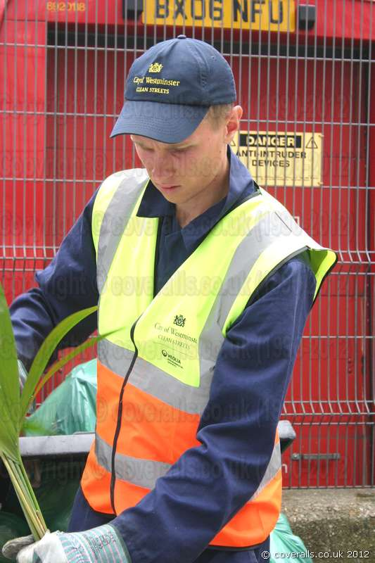 Young blonde lad working as a Road Sweeper wearing a blue boilersuit/coverall and yellow-orange hi-vis waistcoat. Young Blonde Road Sweeper Wearing Blue Boilersuit 14
