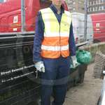 Young blonde lad working as a Road Sweeper wearing a blue boilersuit/coverall and yellow-orange hi-vis waistcoat